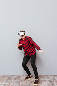 Full length surprised young man in virtual reality device. Isolated gray background
