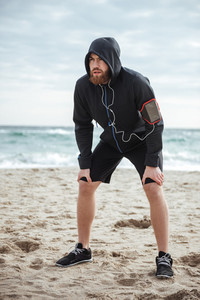 Full length tired runner on beach. looking away