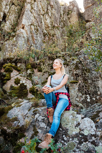 Full length traveling girl with backpack sitting on rock and looking away