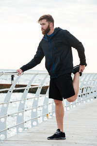 Full length warming up runner. near the sea. looking away