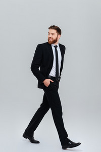 Full length young bearded business man in black suit moves with hands in pockets in studio and looking back. Side view. Isolated gray background