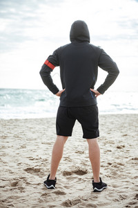 Full length young runner on beach. back view
