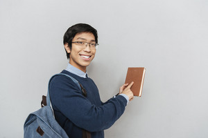 Funny asian student with book. stands sideways