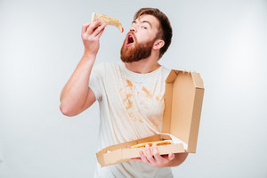 Funny bearded hungry man eating pizza isolated on white background