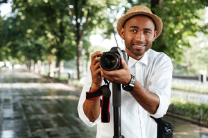 Funny black man in park with camera and hat