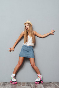 Funny cheerful girl in hat and roller skates having fun isolated on a gray background