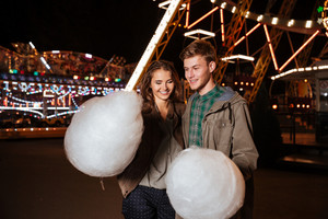 Funny couple in amusement park with cotton candy. in warm clothes