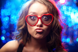 Funny girl wearing heart-shaped glasses at party
