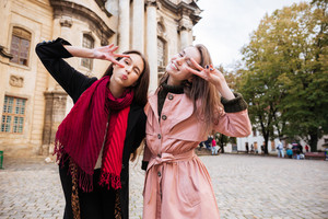 Funny girls in coats on the street. grimace