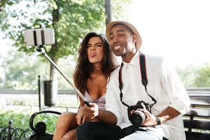 Funny hipster with model in park. makes selfie