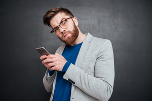 Funny hipster with phone. looking at camera. isolated black background
