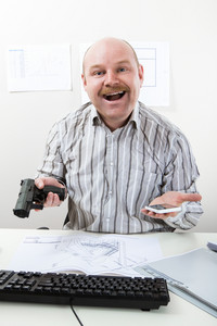 Funny Man Holding Handgun And Mobile Phone At Desk