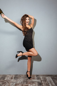Funny model with champagne. full length. in black dress