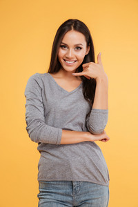 Funny model with hand near the face. looking at camera. isolated orange background