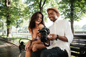 Funny photo session in park with black man. sitting on a bench