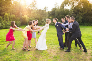 Funny portrait of newlywed couple kissing, bridesmaids and groomsmen pulling them away in green sunny park