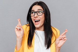 Funny woman wearing eyeglasses and dressed in yellow jacket crossed fingers over grey background. Look aside.