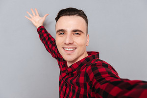 Funny young man in shirt making selfie and posing with hand on background. Isolated gray background