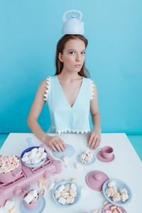 Funny young woman with teapot on her head sitting at the table with marshmallows and plastic tableware over blue background