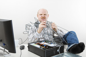 Furious Businessman Holding Tangled Cables Of Computer At Desk