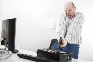 Furious mature businessman aiming gun on CPU at desk in office