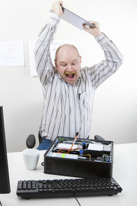 Furious mature businessman banging file on computer chassis at table in office