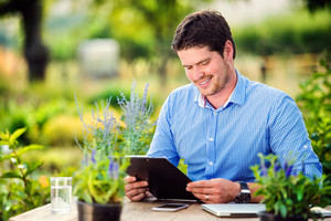 Gardener sitting at the table, holding a clipboard, managing supplies, green sunny nature