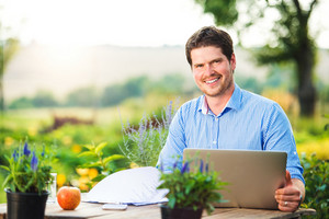 Gardener with notebook sitting at the table, managing supplies, green sunny nature