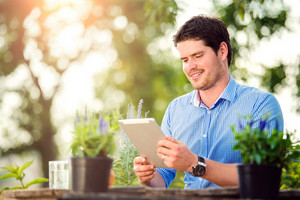 Gardener with tablet sitting at the table, managing supplies, green sunny nature