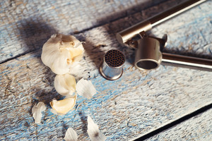 Garlic press and cloves of garlic laid on a wooden table background