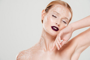 Gentle model with body art and eyes closed. Close up. isolated gray background