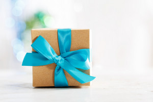 Gift box with blue ribbon in white wall room