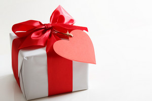 Gift box with red satin ribbon and heart tag