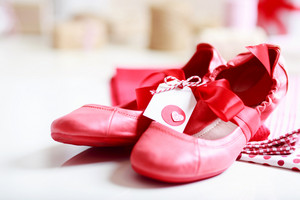 Gift wrapped girls red shoes with ribbon and heart tag