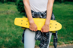 Girl holding a yellow plastic skateboard in the park. She is dressed in a white t-shirt, plaid shirt and jeans.