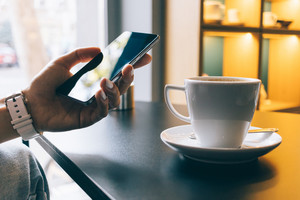 Girl in a cafe using a mobile phone and drinking coffee, close-up