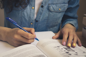 Girl in a denim shirt sitting at the table, reading a textbook and taking notes with a pen on a sheet of paper.