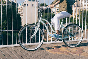 Girl in a jeans jacket and sneakers rides the bridge on a bicycle on a sunny day