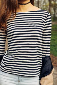 Girl in a striped T-shirt and brown hair outdoors closeup