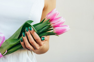Girl in a white dress holding tulips on a light background