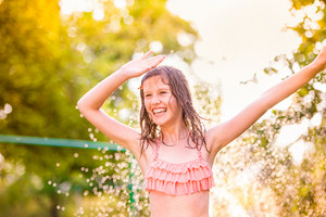 Girl in bikini dancing at the sprinkler, green sunny summer garden
