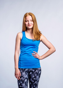 Girl in blue singlet and fitness leggings, young woman, arm on hip, studio shot on gray background