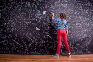 Girl in blue striped t-shirt and red trousers, with two braids, writing on a big blackboard with mathematical symbols and formulas, rear view