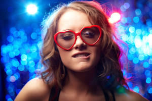 Girl in heart-shaped glasses smiling seductively at camera