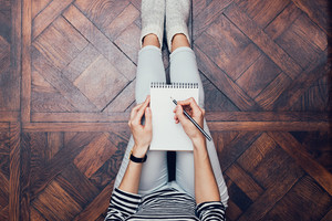 Girl in jeans is sitting at home on the floor and writes with a pencil in a notebook, top view