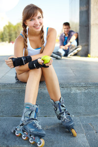 Girl in roller skaters sitting in the foreground and smiling at the cam, her male friend being in the background
