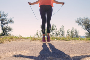 Girl in sportswear and sneakers jumping with a skipping rope on in the summer of the sea background, toned image