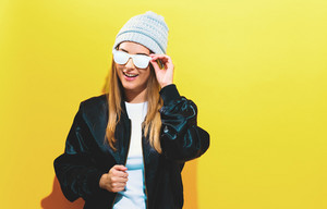 Girl in trendy painted glasses in black jacket on a yellow background