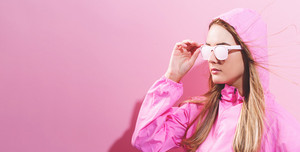 Girl in trendy painted glasses in pink jacket on a pink background