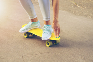 Girl rides on the road on a plastic skateboard in the sunlight, yellow colors